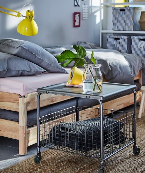 Nutze den Platz in deinem kleinen Schlafzimmer optimal aus! Zum Beispiel mit einem Couchtisch, unter dem du in einem Korb tagsüber Kissen und VÅRELD Tagesdecke in Dunkelgrau unterbringen kannst.