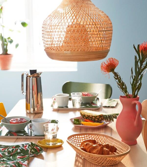 Nyárias hangulatú kiegészítők az étkezőasztalon, bambuszból készült lámpa és tálca.