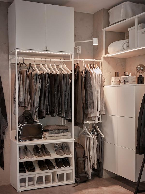 Nyitott fehér gardróbmegoldás, ruhasínekkel, cipős polcokkal, fali tárolóval, világító szalaggal és dobozokkal.