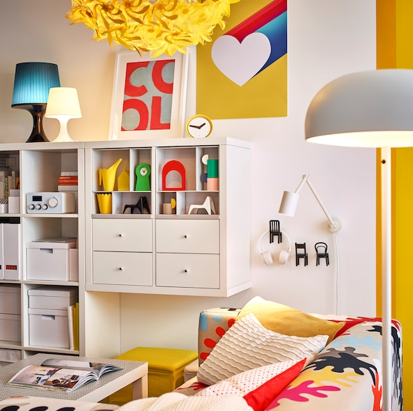 NYMÅNE مصباح أرضي أبيض وGRIMSÅS مصباح معلق أصفر من ايكيا يضيئان غرفة جلوس بيضاء.
