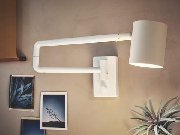 NYMÅNE wandlamp steekt uit van een beige wand waar fotootjes ophangen en verspreidt gericht licht.