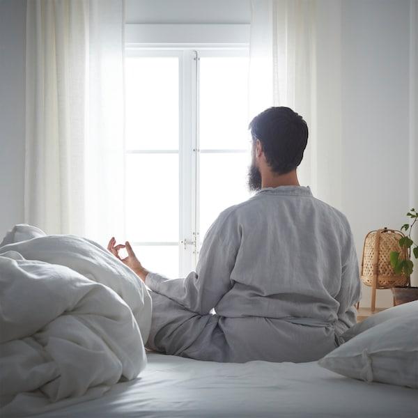 Nyugodt hangulatú hálószobában egy szakállas férfi keresztbe tett lábakkal ül az ágyon meditáló pózban, és közben kinéz az ablakon.