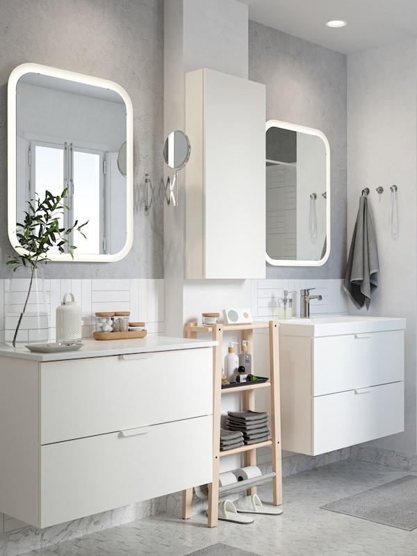 O baie alb-gri cu două lavoare și oglinzi GODMORGON. Între ele se află un corp cu rafturi VILTO din mesteacăn.