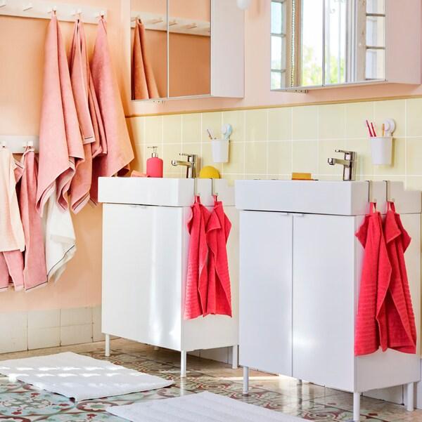 O baie cu două lavoare albe și dulapuri oglindă LILLÅNGEN, cu prosoape de baie și de mâini roz care atârnă în cârlige.