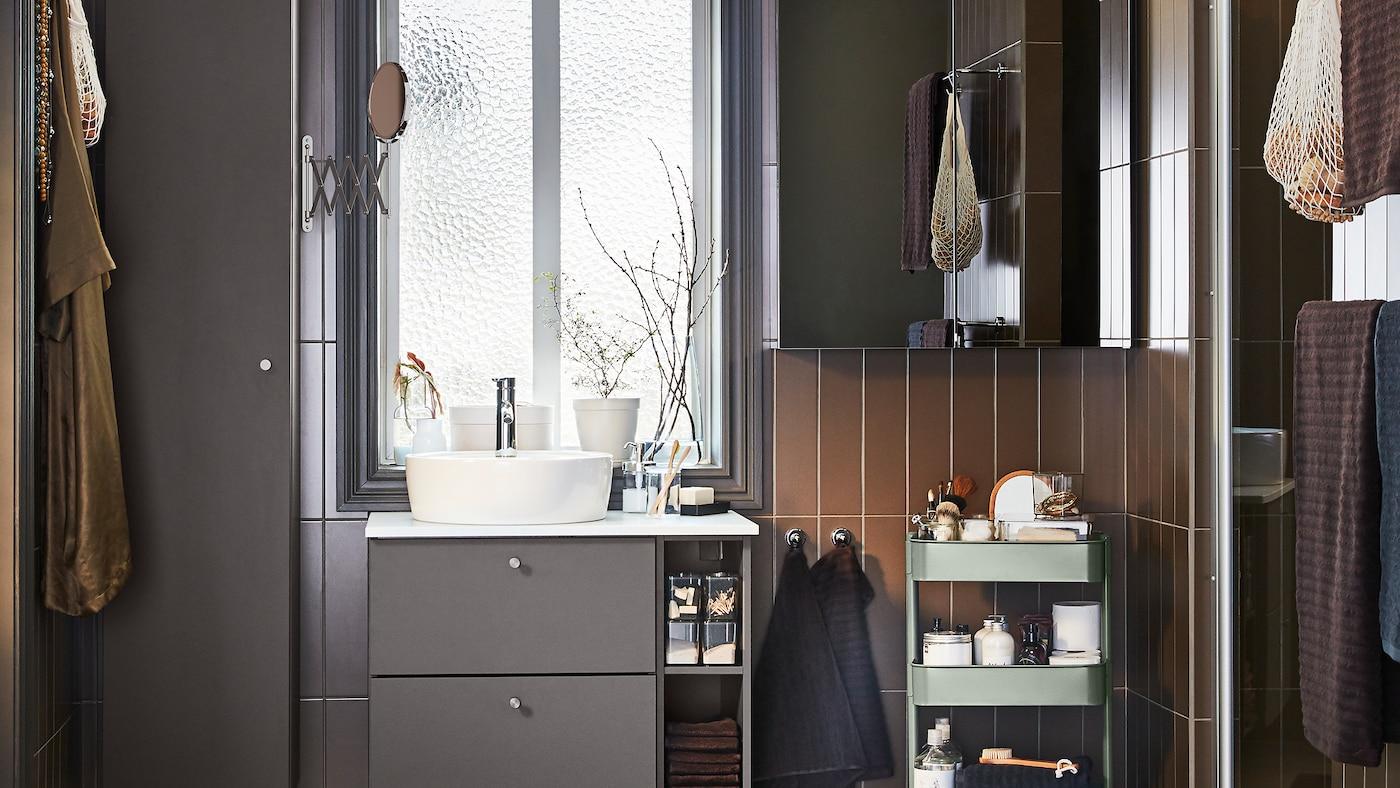 O baie cu mobilier de baie gri închis, un dulap cu ușă cu oglindă și un cărucior gri-verde.