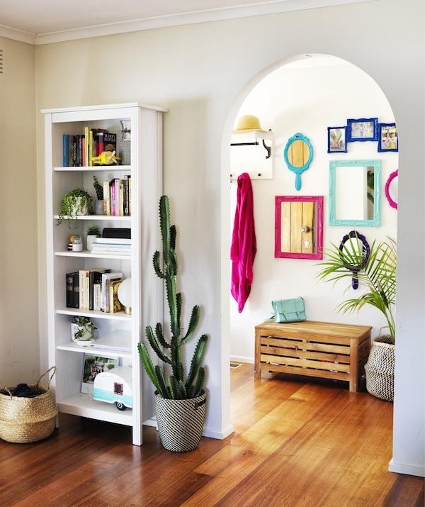 O bibliotecă albă și un cactus mare lângă o arcadă care duce la un hol cu oglinzi colorate pe perete.