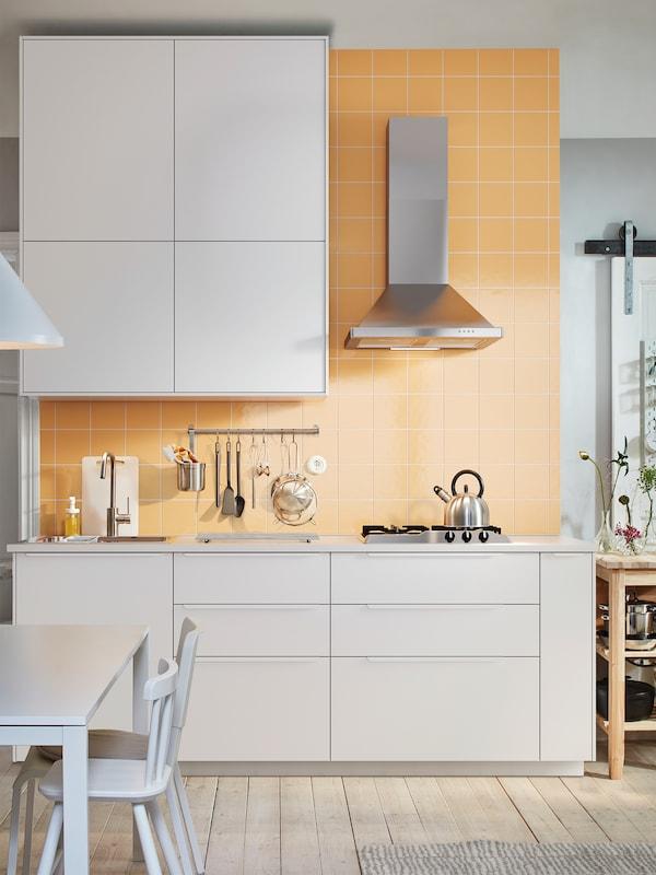 O bucătărie albă cu dulapuri albe, o hotă din inox montată pe perete și o masă albă cu scaune.