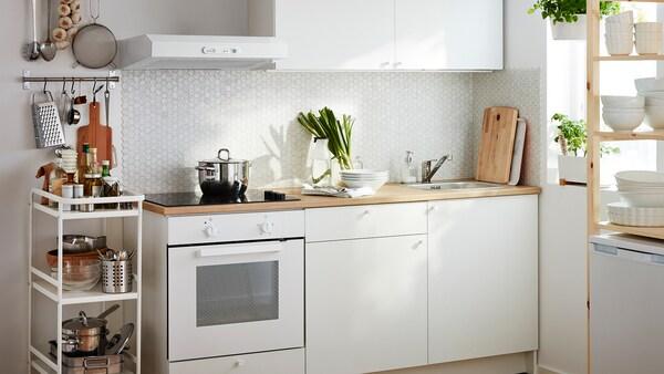 O bucătărie albă mică, compusă dintr-un cuptor încorporat și dulapuri de bază, sertare, un blat și un dulap de perete.