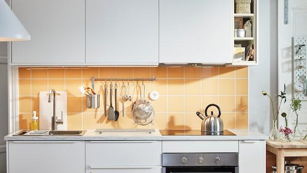 O bucătărie albă mică cu fronturi de dulap albe VEDDINGE și plăci portocaliu-galben, o plită și un suport cu ustensile.