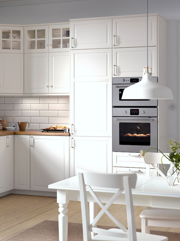 O bucătărie BODBYN pe alb în stil tradițional, masă de bucătărie albă și două scaune și o lustră RAGNARP.