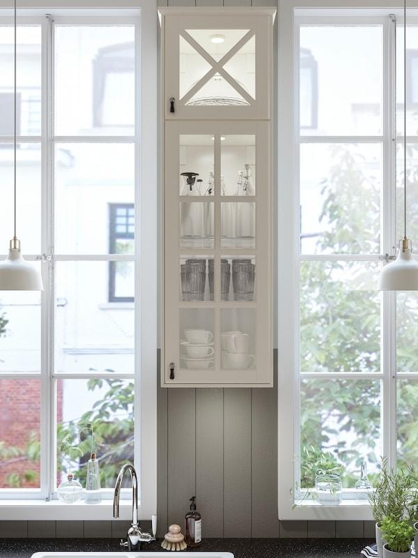 O bucătărie cu dulap îngust în nuanțe de alb, cu uși de sticlă, între două ferestre și un blat negru cu efect mineral.