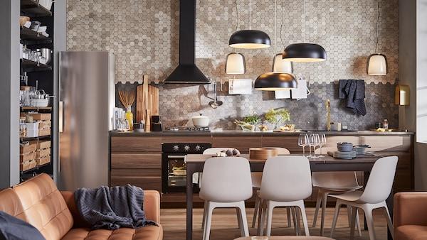 O bucătărie cu dulapuri din lemn cu efect de nuc maro închis, trei lustre negre, o masă maro închis și șase scaune.