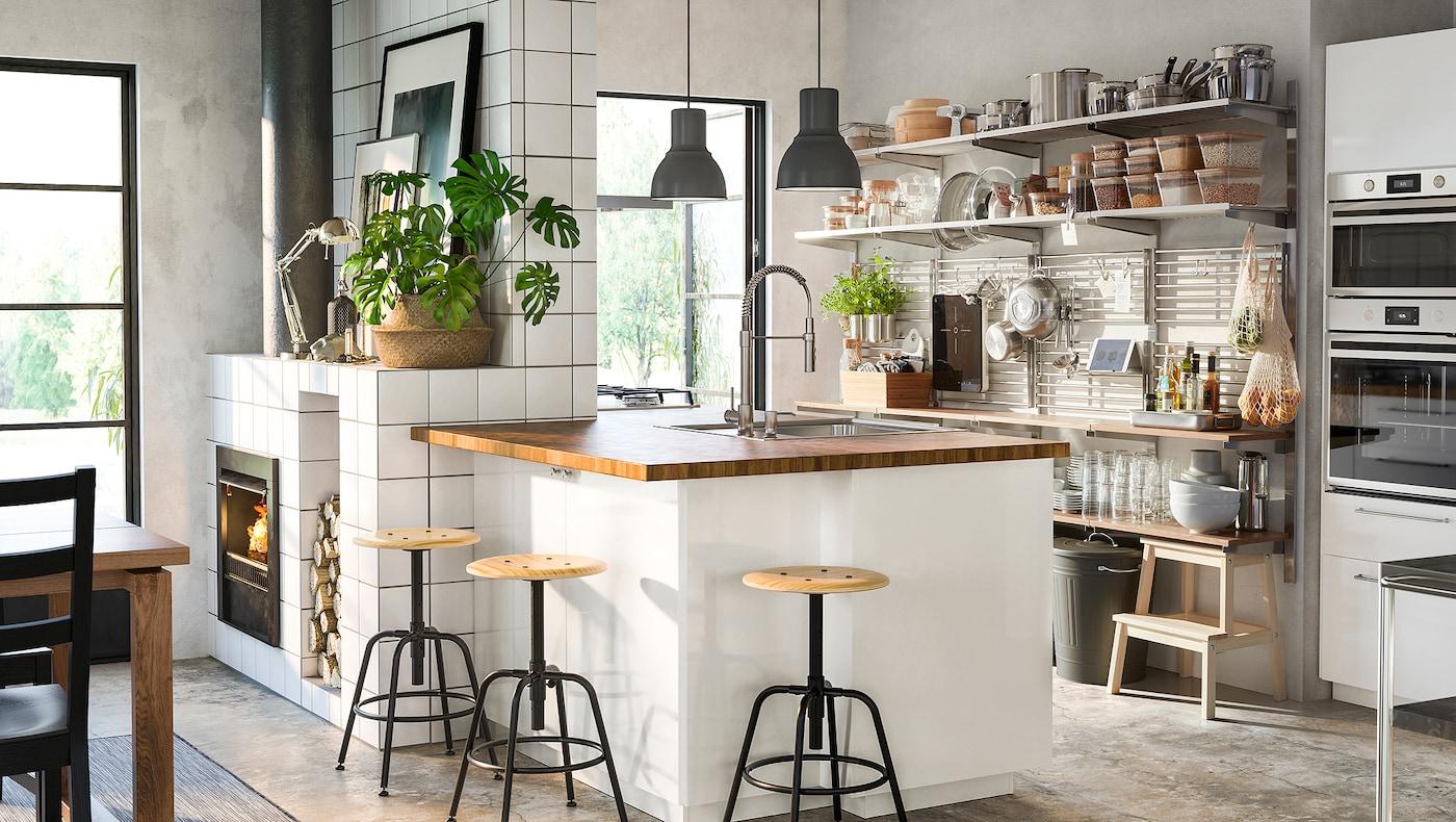 O bucătărie cu o insulă alb/lemn cu luciu puternic, un grilaj din inox cu rafturi montat pe perete și taburete culoare pin/negru.