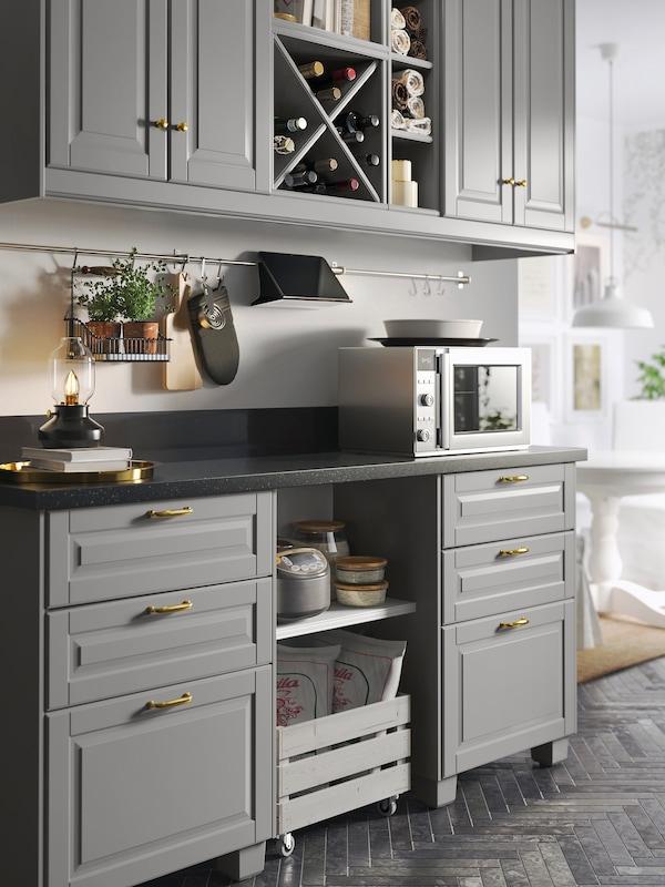 O bucătărie cu patru uși de dulap gri, un blat negru cu efect mineral și dulapuri de bază cu șase fronturi de sertar gri.