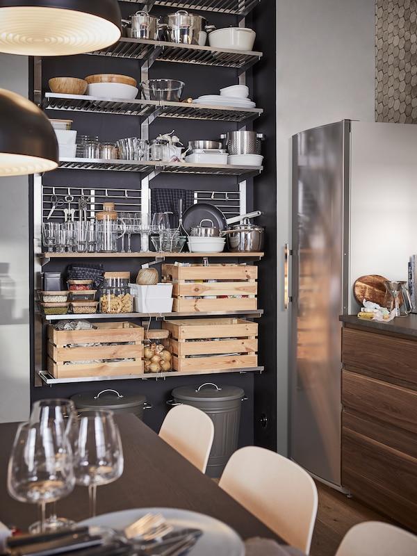 O bucătărie cu un corp de rafturi de depozitare din inox, unde se află recipiente, veselă și trei cutii din pin.