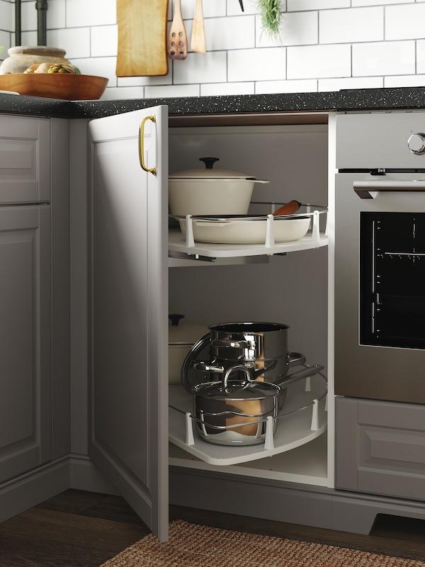 O bucătărie cu uși gri și un dulap de colț deschis în care sunt depozitate oale, cratițe și vase într-un carusel.