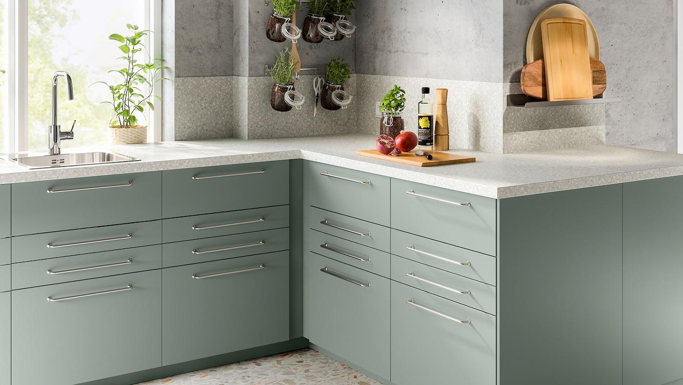 O bucătărie de colț cu un blat gri deschis cu efect mineral și câteva dulapuri cu fronturi de sertare cu folie gri-verde.