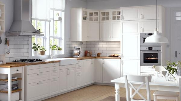 O bucătărie de colț cu uși și fronturi de sertare BODBYN în nuanțe de alb și uși de sticlă tip vitrină cu bare transversale.