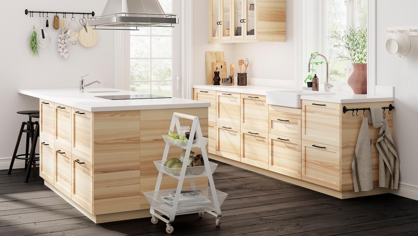 O bucătărie deschisă cu uși tradiționale din frasin natural și sticlă și dulapuri din frasin, o insulă de bucătărie i o podea din lemn închis la culoare.