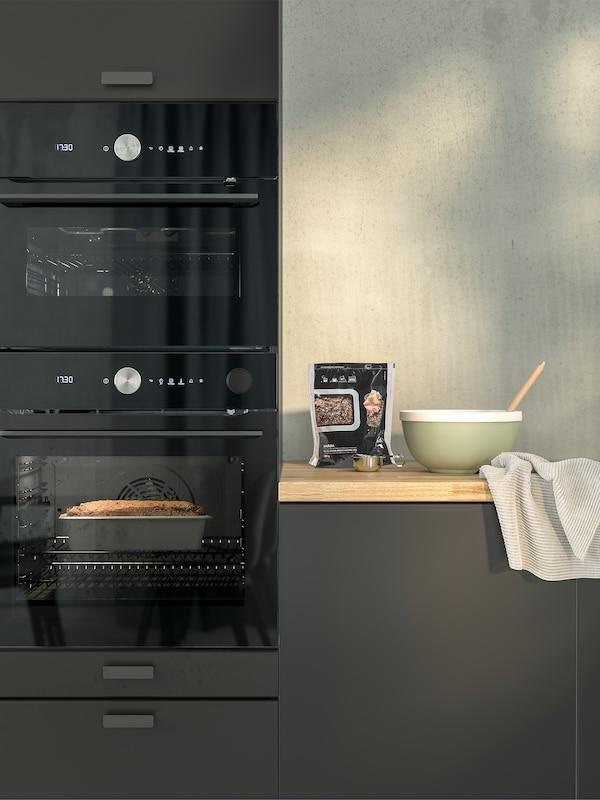 O bucătărie gri cu cuptor cu încălzire forțată și microunde FINSMAKARE, un bol și o pungă de crutoane pe un blat.