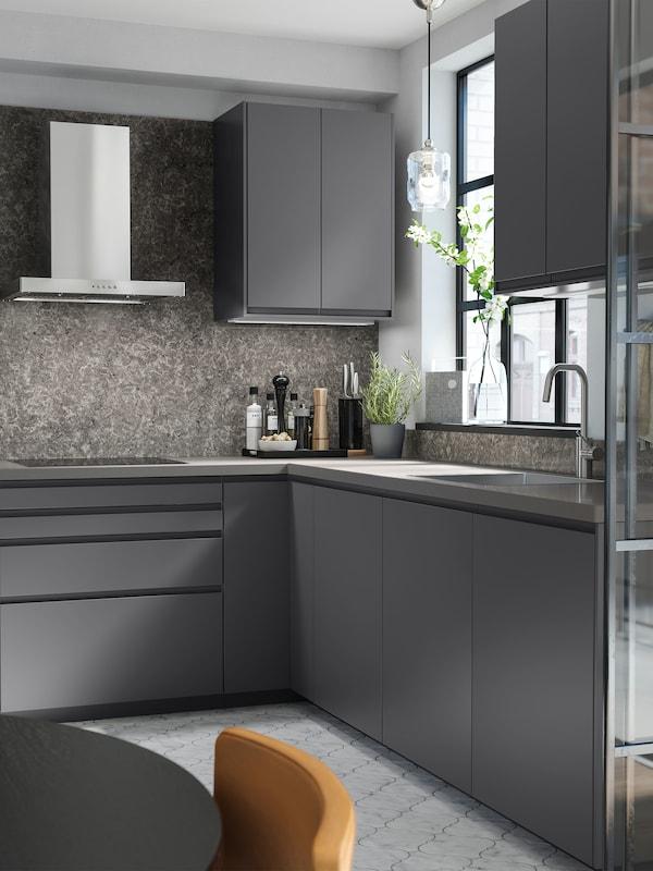 O bucătărie gri închis cu dulapuri gri închis, o hotă de perete din inox și o podea cu model.