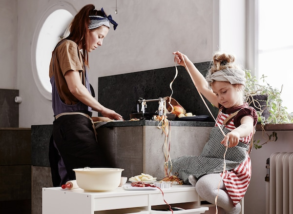O bucătărie în care mama spală vasele, în timp ce fetița ei asamblează o ghirlandă.
