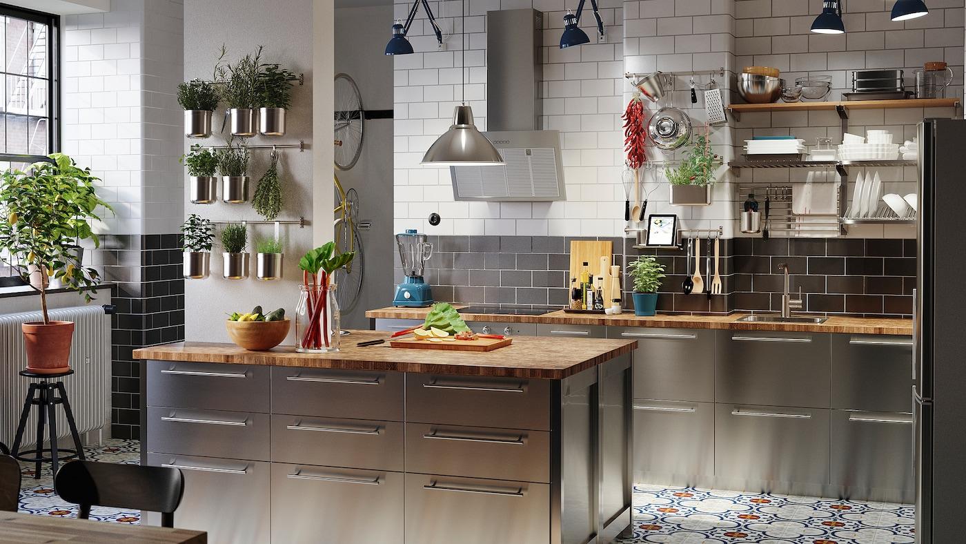 O bucătărie mare cu fronturi din inox, blaturi din stejar/placaj, lămpi de birou albastre și plante aromatice în recipiente.