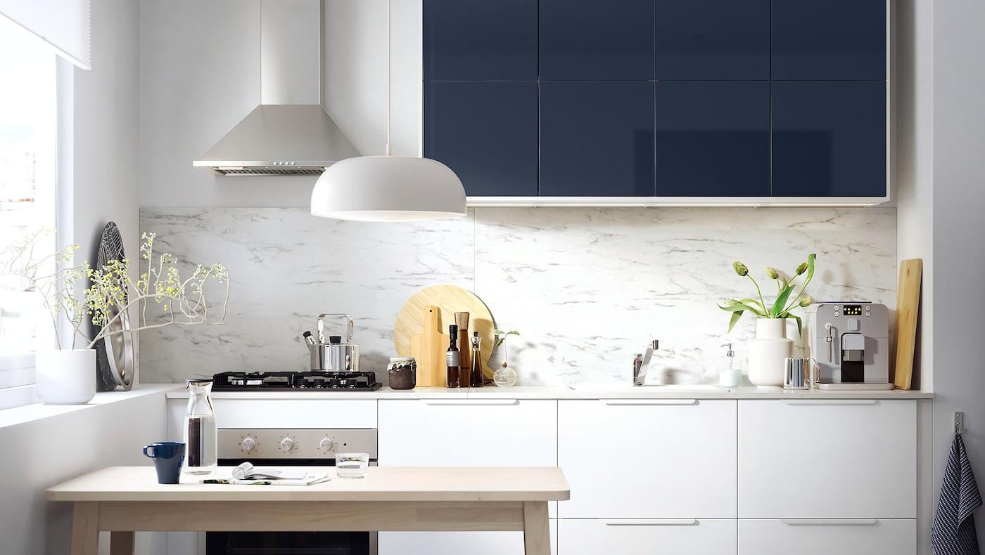 O bucătărie mică cu sertare albe și fronturi de dulapuri de bucătărie pe albastru-negru, și o masă din lemn.
