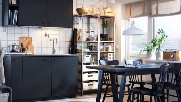 O bucătărie monocromă elegantă cu dulapuri antracit, o masă și scaune negre și rafturi metalice deschise.