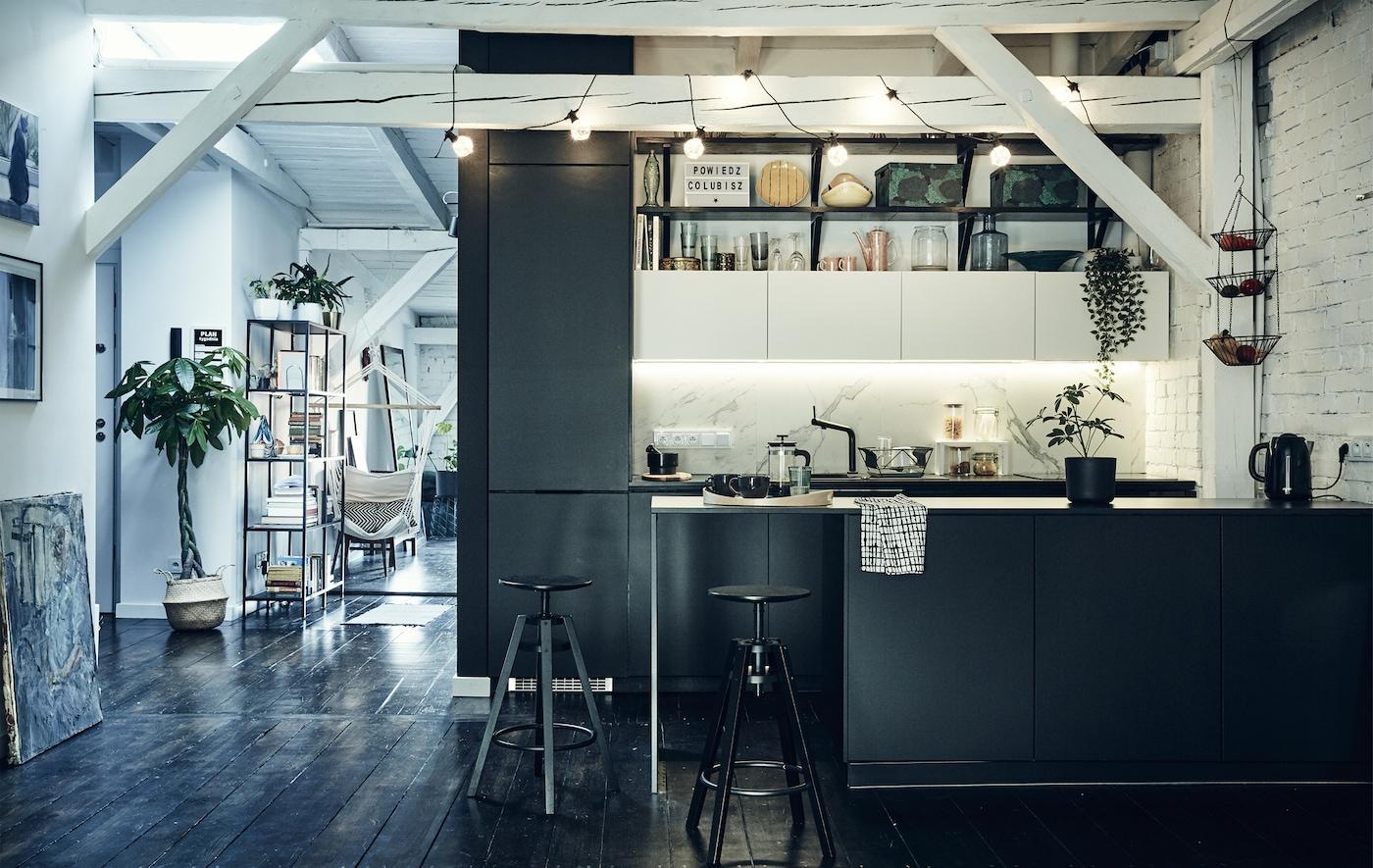 O bucătărie neagră într-un spațiu deschis cu raze albe pe tavan și podele de lemn închis la culoare.