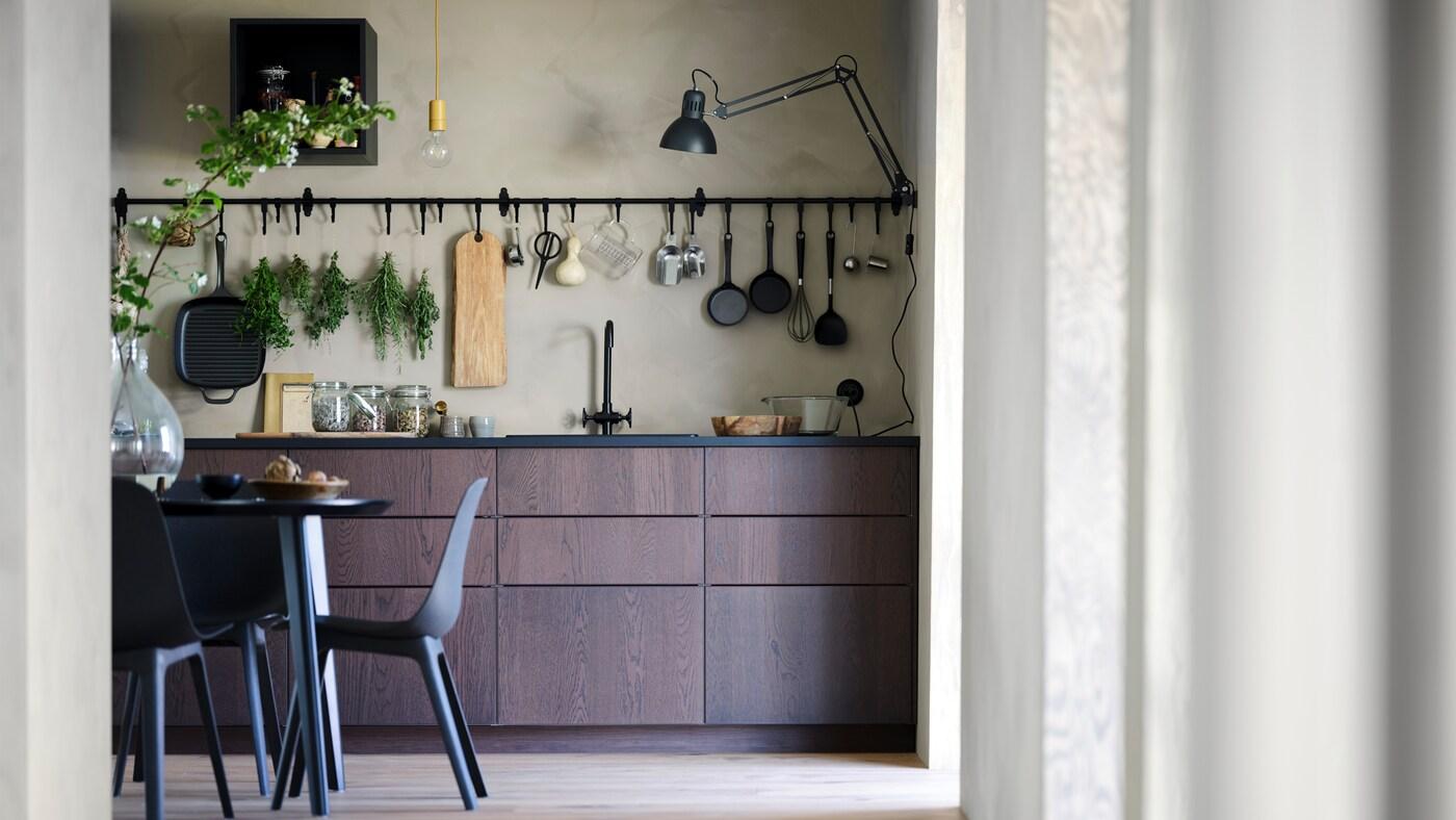 O bucătărie SINARP cu masă și scaune și o șină și cârlig HULTARP agățat de perete.