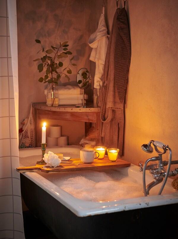 O cadă de baie plină cu bule spumoase, cu o scândură de lemn cu lumânări și alte articole pe latul căzii.