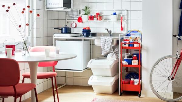O cameră cu o mini-bucătărie albă SUNNERSTA, un cărucior roșu, electrocasnice TILLREDA, o masă cu scaune roșii și o bicicletă.
