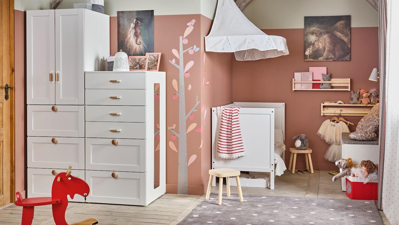 O cameră de copii tradițională albă/roz, cu ansamblu de depozitare SMÅSTAD/PLATSA, un pătuț SUNDVIK și taburete pentru copii FLISAT.
