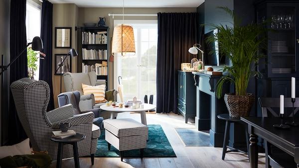 O cameră de zi cu două scaune cu brațe cu model ecosez, un covor verde, o lustră din bambus și o măsuță de cafea rotundă.