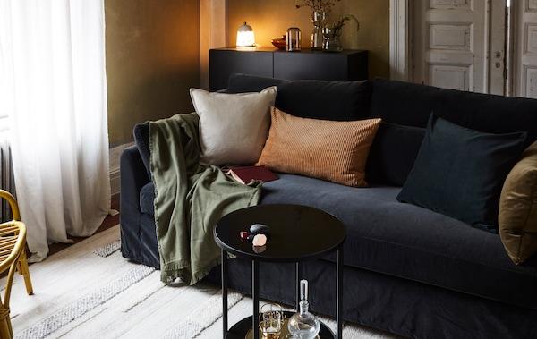 O cameră de zi cu o canapea, perne, pătură, covor, o măsuță, o comodă cu o veioză, vaze și un fotoliu din ratan.