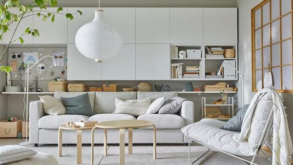 O cameră de zi luminoasă, cu un scaun ușor, multe corpuri albe montate pe perete și o lustră rotundă albă.