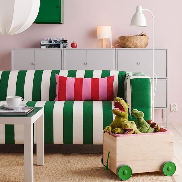O canapea cu dungi verzi și albe, o pernă cu dungi roșii și roz, o cutie de jucării de pluș și ceva produse de depozitare.