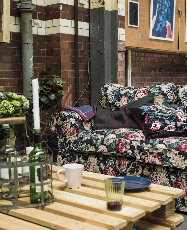 O canapea cu motive florale și o masă din paleți într-un spațiu industrial.