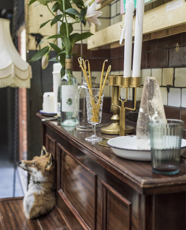 O canapea cu motive florale și o masă din paleți într-un spațiu industrial. Un pian, sfeșnice, lumânări și articole de sticlărie.