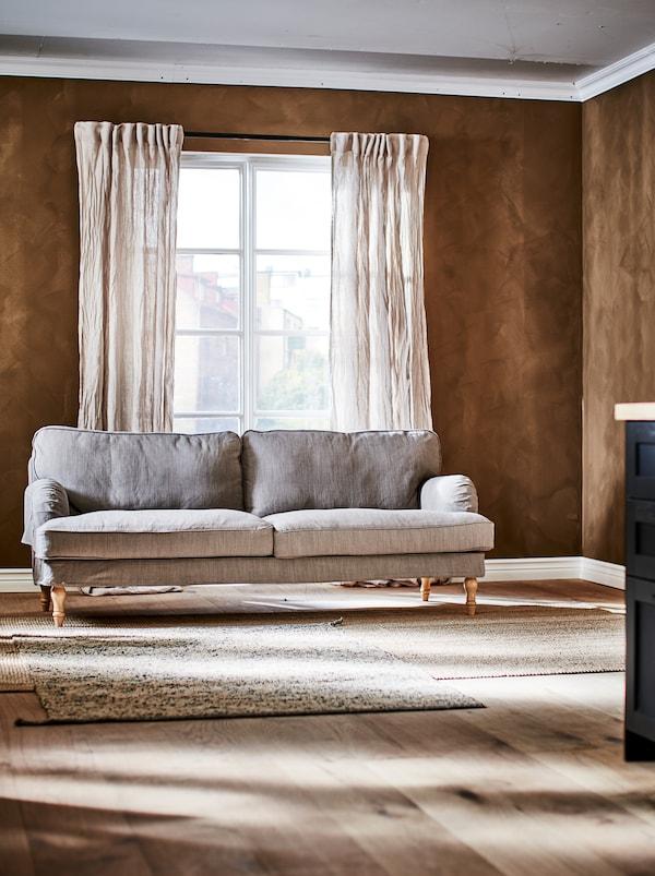 O canapea cu trei locuri într-o încăpere maro cu ferestre în stil franțuzesc, cu perdele din in creponat și un covor MELHOLT pe pardoseala din lemn.