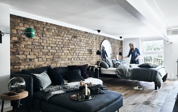 O canapea extensibilă în faţa unui perete de cărămidă.