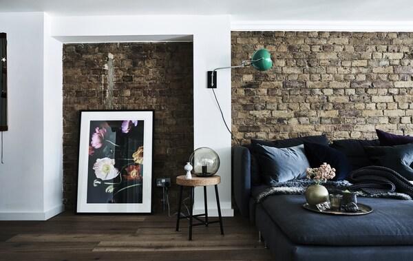 O canapea în faţa unui perete negru.