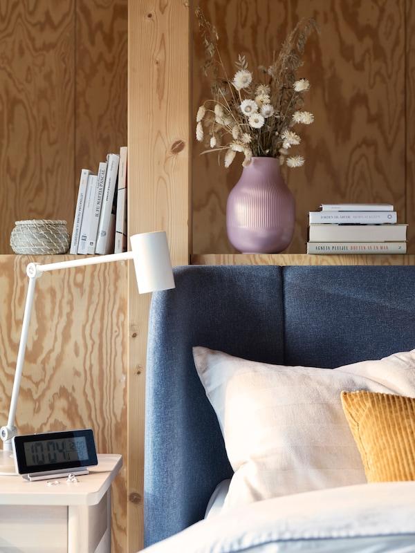 O canto arredondado de uma cama TUFJORD azul, em frente a uma parede de madeira com uma estante integrada e ao lado de uma mesa de cabeceira.