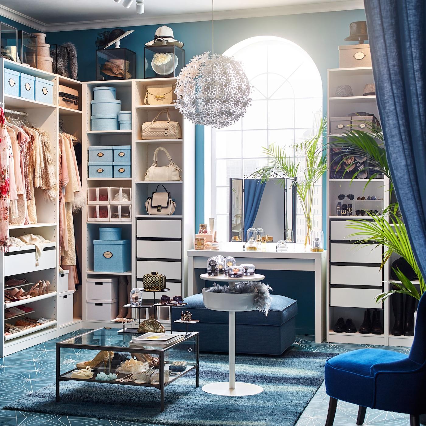 O closet está decorado com roupeiros da gama PAX, em branco, e em tonalidades escuras como o azul do repousa-pés KIVIK e o azul esverdeado da poltrona REMSTA.
