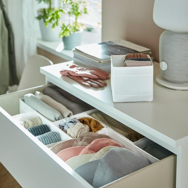 O comodă MALM albă, cu un sertar deschis. În sertar se află cutii SKUBB, folosite pentru sortarea obiectelor. Veioza SYMFONISK este așezată pe comodă.