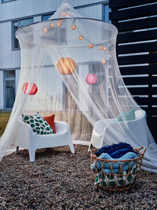 O curte amenajată cu o plasă SOLIG decorată care acoperă fotolii de plastic. Un coș SNIDAD cu perne și pături este așezat pe jos în apropiere.