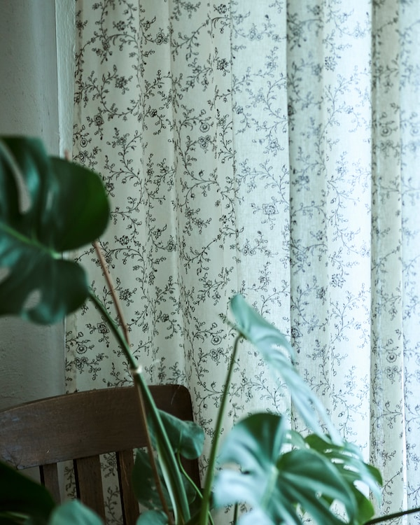 O draperie albă cu un delicat imprimeu botanic suspendată la fereastră, lângă care se află un scaun de sufragerie din lemn închis la culoare și o plantă MONSTERA.