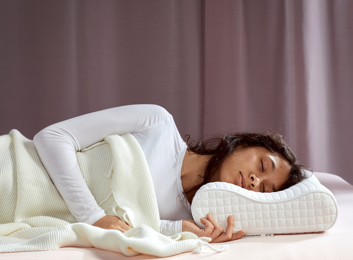O femeie cu păr șaten și cămașă albă dormind sub o pătură albă pe o pernă ergonomică ROSENSKÄRM.
