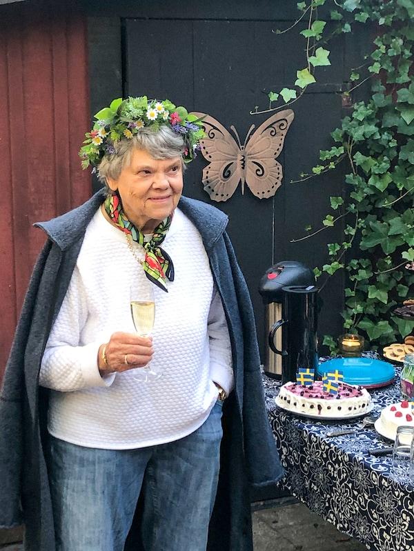 O femeie cu părul cărunt, cu o coroană de flori pe cap, stă în aer liber, ținând în mână un pahar de șampanie.